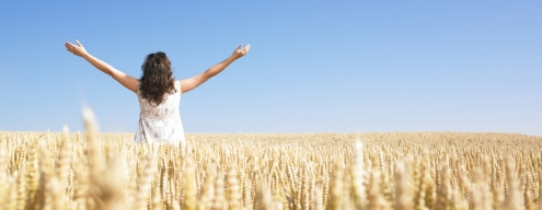 A woman standing in wheat field with arms outstretched. Horizontally framed shot.
